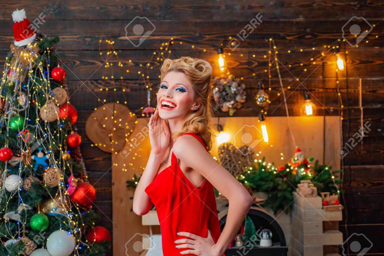 Beautiful pinup girl celebrated Christmas holiday with pin-up makeup and hairstyle. Smiling woman in evening red dress over home Christmas tree background. Beauty fashion Christmas fashion model.